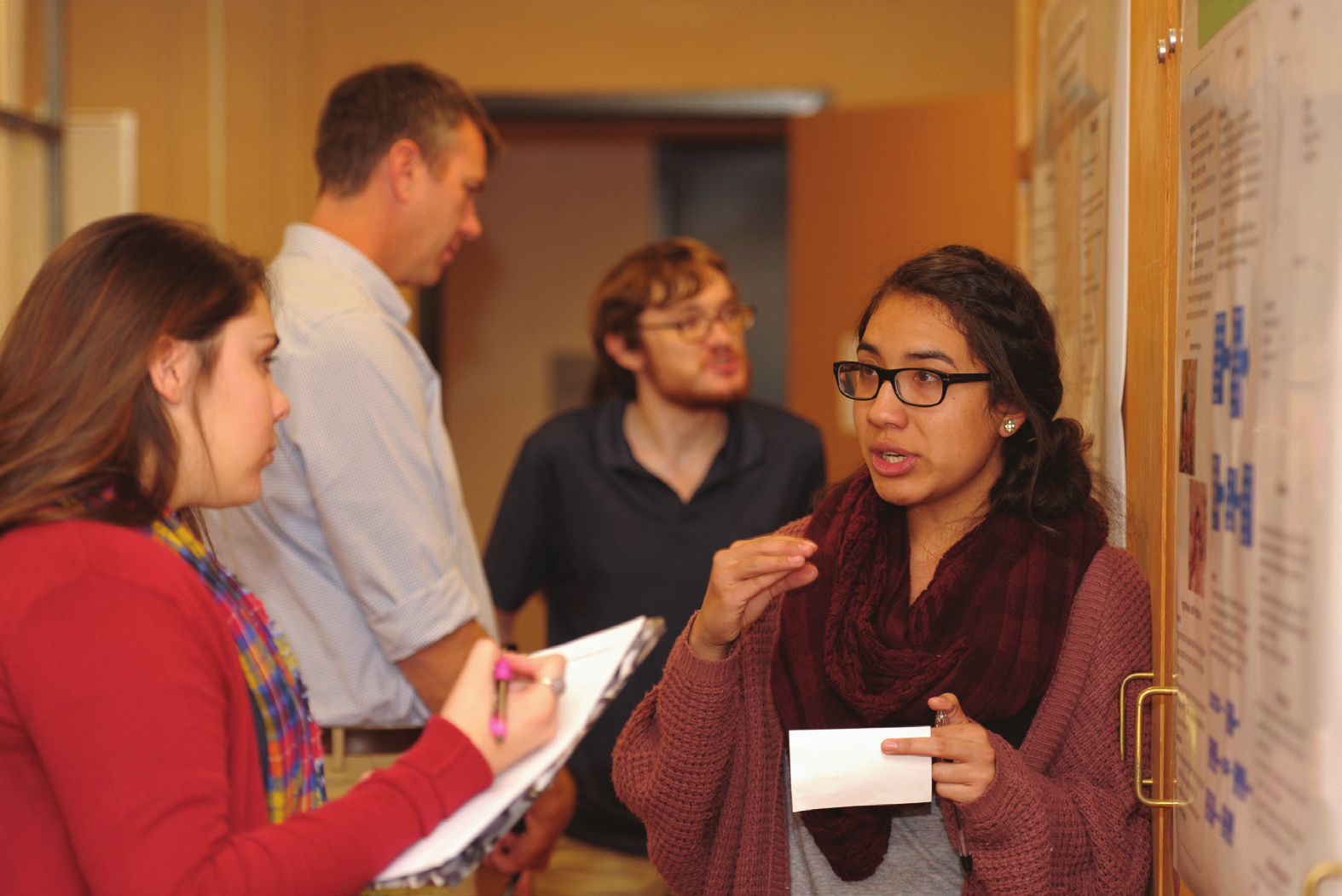 NMSU biology student Nubia Bermudez, right, presents her research poster to Darien Pruitt, left, during the lab component of an NMSU-HHMI undergraduate guided biological research class in Foster Hall. Student Matthew Griffin appears in the background presenting his poster to biology professor Tim Wright.
